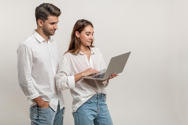 흰색 배경에 격리된 비디오를 보고 있는 노트북을 사용하는 매력적인 학생들의 초상화