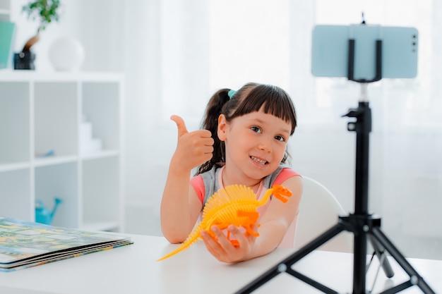 엄지손가락으로 확인 표시를 하고 스마트폰에 공룡 장난감을 보여주는 매력적인 즐거운 소녀의 초상화