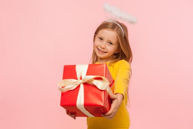 Портрет очаровательной добрая рыжая девочка с веснушками и ангельским ореолом держит большую подарочную коробку, поздравляет с праздником и дарит подарок на день рождения. закрытый студийный снимок изолирован на розовом фоне