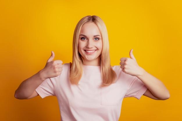 웃는 미소를 짓는 매력적인 여성의 초상화는 노란색 배경에 두 개의 엄지손가락을 들어 승인합니다.