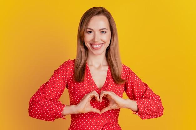 Портрет очаровательной дамы сформировал фигуру сердца с руками на желтом фоне