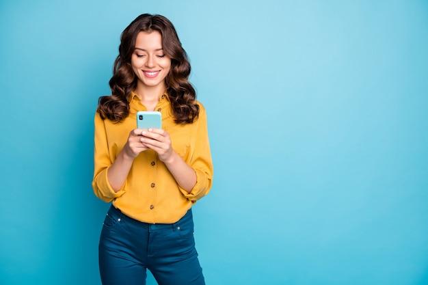 새로운 긍정적 인 댓글을 읽고 전화 손을 잡고 매력적인 아가씨의 초상화 인스 타 그램 블로그 게시물 착용 노란색 셔츠 바지.