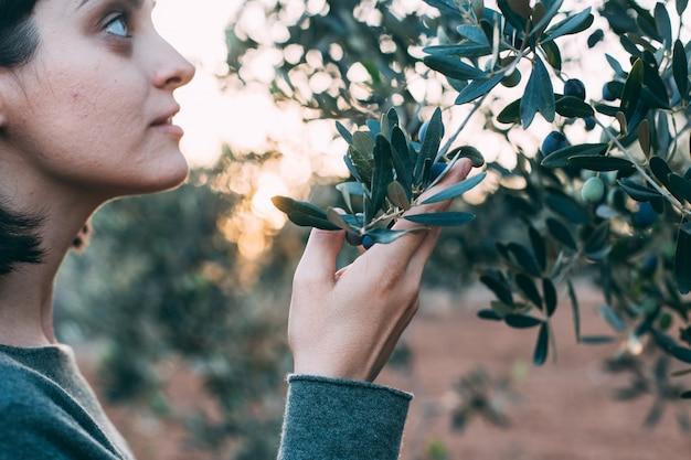 オリーブの木の横にポーズをとって夏のリゾートの衣装で魅力的な女性の肖像画