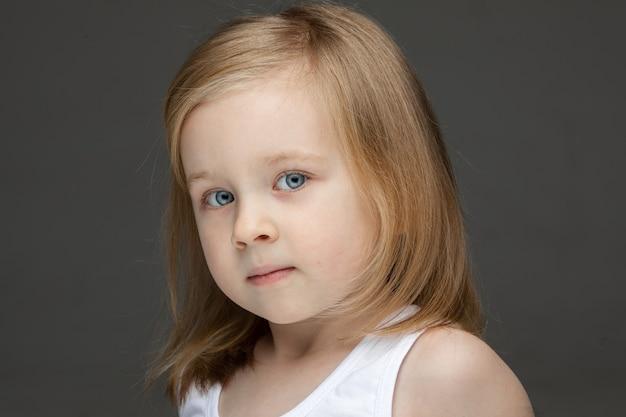 Портрет очаровательной маленькой девочки со светлыми волосами средней длины, смотрящей в камеру голубыми глазами. изолированные на серой стене.