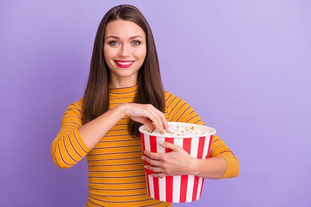 Портрет очаровательной милой милой девушки, держащей полосатую коробку с попкорном, ест смотреть интересный фильм, носить повседневный стиль, красивый свитер, изолированный на фиолетово-фиолетовом цвете