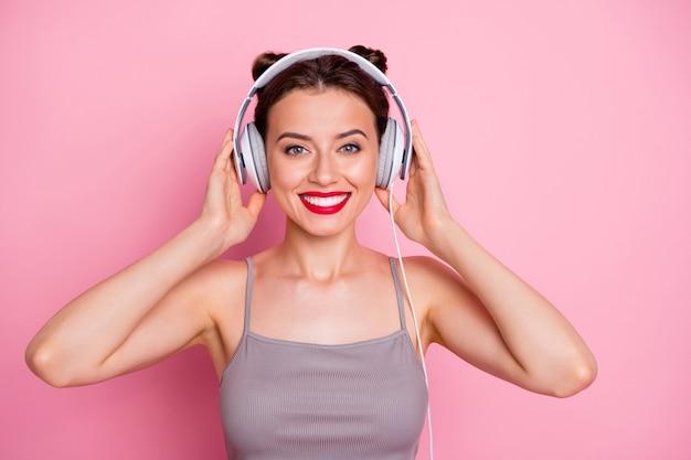 매력적인 사랑스러운 gilr의 초상화는 그녀의 흰 귀 전화로 음악을 듣고 분홍색 색상 위에 고립 된 캐주얼 스타일의 옷을 입는 콘텐츠를 느낍니다.