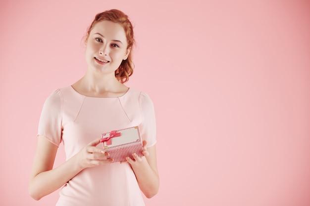작은 선물 상자를 열고 카메라를 보고 있는 매력적인 젊은 여성의 초상화