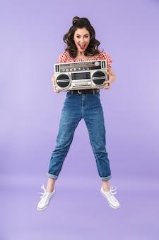Портрет очаровательной женщины в стиле пин-ап в американском стиле радуется, держа в руках старый винтажный магнитофон, изолированный над фиолетовой стеной