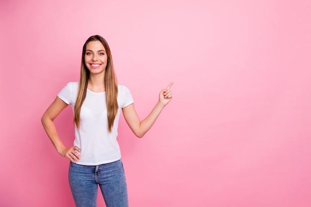 매력적인 긍정적 인 소녀 발기인 포인트 검지 손가락 copyspace의 초상화는 프로모션 광고가 캐주얼 스타일의 옷을 입는 것을 나타냅니다.