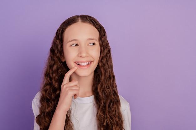紫色の背景の上に分離された指のあごに触れることを考えている魅力的な10代前の少女の肖像画