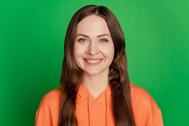 魅力的なかわいい女性の肖像画は、緑の背景にカメラのこぼれるような白い笑顔を見てください