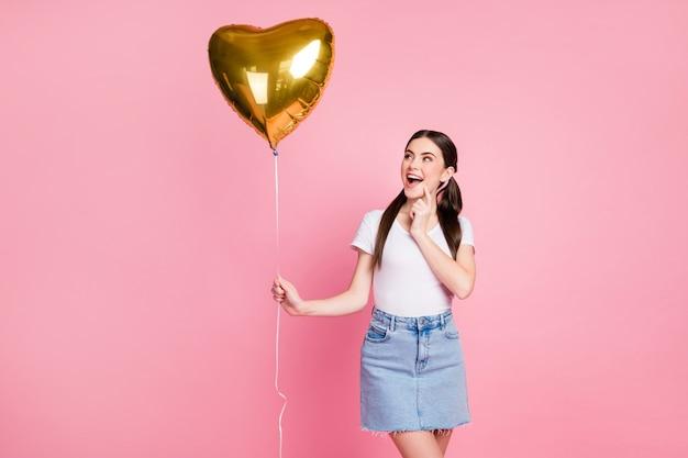 Портрет очаровательной красивой девушки, держащей в руке гелиевый шар, смотрит вверх