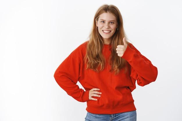 빨간색 따뜻한 스웨터를 입은 매력적인 여성의 초상화는 허리에 손을 잡고 웃고 긍정적인 대답을 하며 아이디어를 좋아하는 엄지손가락 제스처를 보여줍니다.