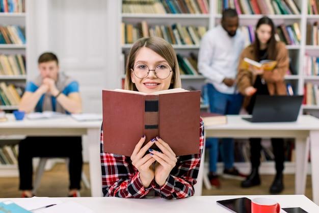 Портрет очаровательной студенческой девочки в повседневной одежде и очках, изучающей в библиотеке, сидящей за столом и держащей открытую книгу около ее лица. друзья смешанной расы исследуют пространство