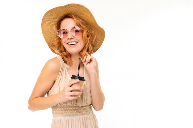 白い壁にお茶の紙コップと帽子の魅力的なスタイリッシュな笑顔の女の子の肖像画