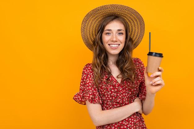 オレンジ色の背景に紙コップと帽子の魅力的なスタイリッシュな笑顔の少女の肖像画
