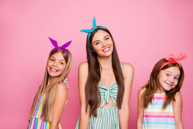 ピンクの背景に分離された明るいヘッドバンドのスカートのドレスを着て輝く素敵な笑顔でポーズをとる魅力的な3人の女の子の肖像画