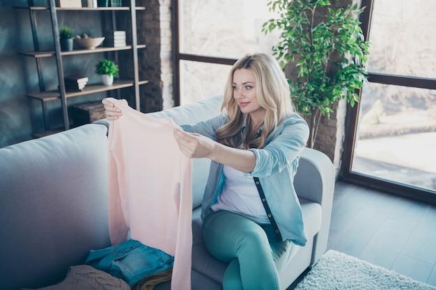 Портрет очаровательной волнистой женщины, сидящей на диване и выбирающей одежду