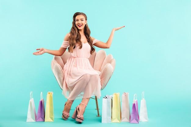 青い壁に分離されたカラフルなバッグがたくさん買い物をした後ピンクのアームチェアに座っている魅力的な女性20代の肖像画