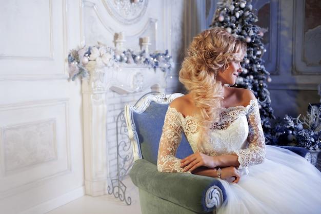 ウェディングドレスの魅力的な女性の肖像画。椅子に座っている少女の花嫁
