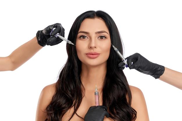 Портрет очаровательной женщины позирует на белом с тремя руками в перчатках, держа шприцы вокруг ее лица