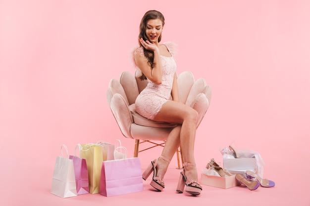 Портрет очаровательной женщины в платье и на каблуках, сидящей в кресле с пакетами для покупок и коробками для обуви, изолированными над розовой стеной