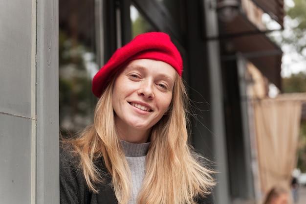 Портрет очаровательной молодой блондинки в красном головном уборе, позитивно выглядящей, позируя на открытом воздухе, находящейся в хорошем настроении и искренне улыбающейся в ожидании своих друзей