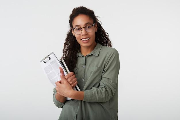 彼女の手に教科書を保持し、白で隔離された広い笑顔で喜んで見ている黒い肌を持つ魅力的な若い黒髪の巻き毛の女性の肖像画