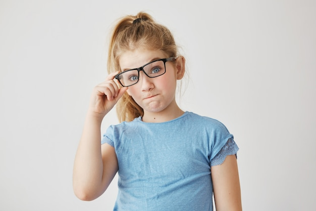 Портрет очаровательной молодой девушки с голубыми глазами и светлыми волосами, улыбающимися, завязывающими мамины очки и весело проводящими время дома одни. копировать пространство
