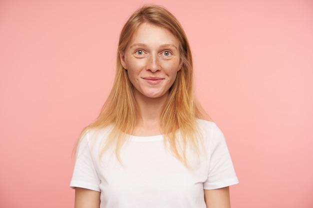 자연 메이크업으로 매력적인 젊은 빨간 머리 아가씨의 초상화는 카메라를 긍정적으로보고 즐겁게 웃고, 손으로 분홍색 배경 위에 포즈를 취합니다.