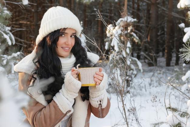 멋진 겨울 숲, 크리스마스와 연말 연시의 개념에서 뜨거운 음료를 마시는 매력적인 젊은 여자의 초상화