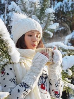 멋진 겨울 숲에서 뜨거운 음료를 마시는 매력적인 젊은 여자의 초상화