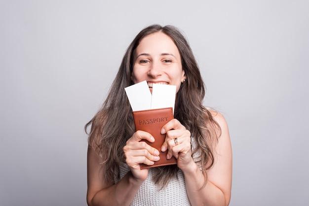 Портрет очаровательной молодой женщины, держащей паспорт с авиабилетами.