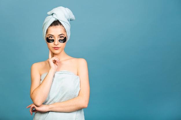 目の下に化粧品のコラーゲンパッチがあり、完璧な肌を楽しんで、肌の色をよく気遣っている魅力的な若い女性の肖像画