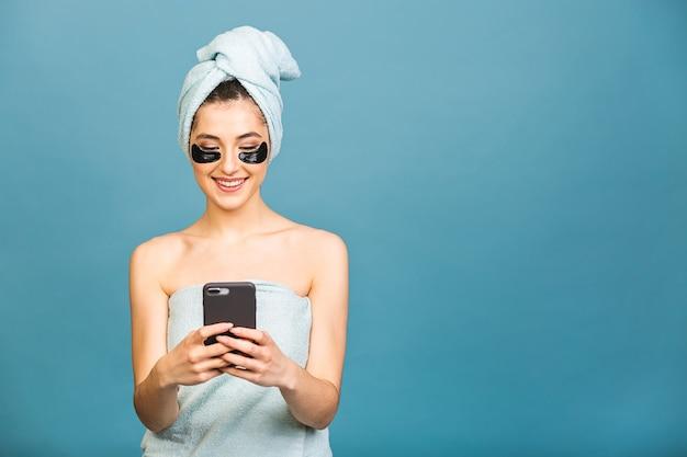 Портрет очаровательной молодой женщины с косметическими пятнами коллагена под глазами, наслаждается безупречной кожей, используя мобильный телефон