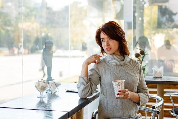 Wiで笑っているニットセーターでフレンドリーな笑顔のブルネットの魅力的な若い女性の肖像画