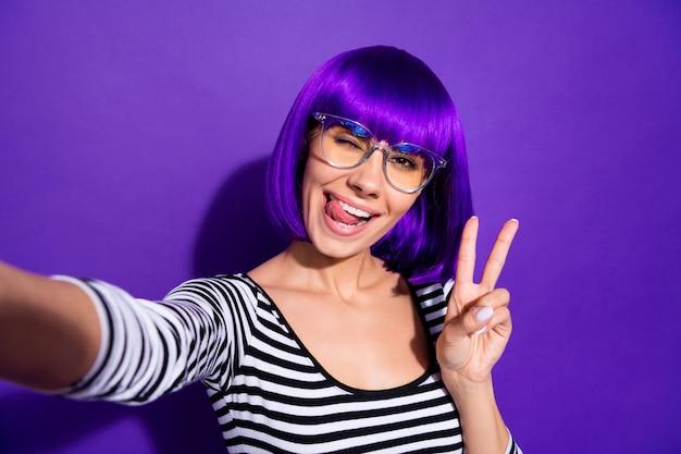 Портрет очаровательной молодежи, делающей фото v-знаков в полосатой рубашке, изолированной на фиолетово-фиолетовом фоне