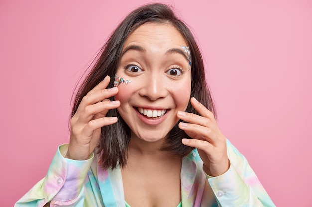 Портрет жизнерадостной азиатской женщины с зубастой улыбкой наслаждается, когда слышит позитивные новости, трогает свежую кожу с наклеенными на лицо блестящими камнями, выражает счастливые подлинные эмоции, изолированные на розовой стене