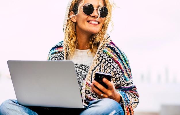 ローミング技術で携帯電話とラップトップコンピューターで屋外で働く陽気な大人の白人女性の肖像画-オフィスライフスタイル現代人の概念から解放されます