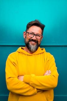 陽気な大人のハンサムな男の肖像画は、黄色いセーターの服とバックゴーランドの青い壁で笑顔-幸せな人々とコピースペース-黒い目の眼鏡をかけたひげ50歳の男性