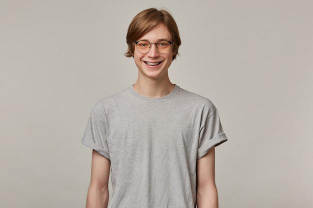 금발 머리를 가진 쾌활한, 성인 남자의 초상화. 회색 티셔츠, 안경을 착용하고 교정기가 있습니다. 사람과 감정 개념. 회색 벽에 고립 된 미소