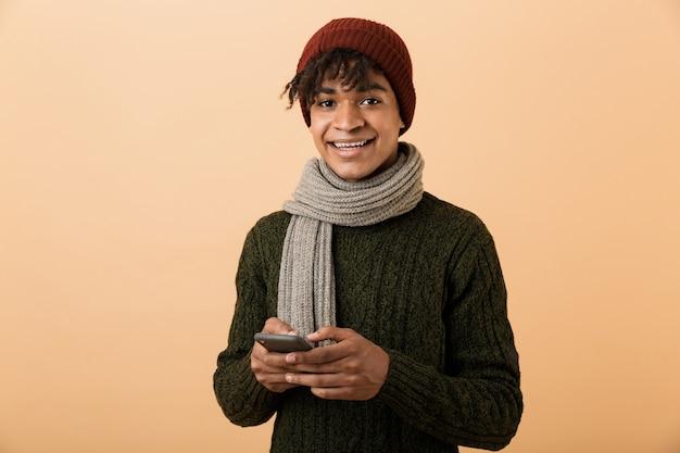 黄色の壁に隔離された携帯電話を使用して帽子とスカーフを身に着けている陽気なアフリカ系アメリカ人男性の肖像画