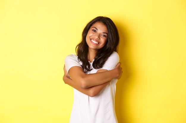 自分を抱きしめて、黄色の上に立って喜んで笑顔の陽気なアフリカ系アメリカ人女性の肖像画