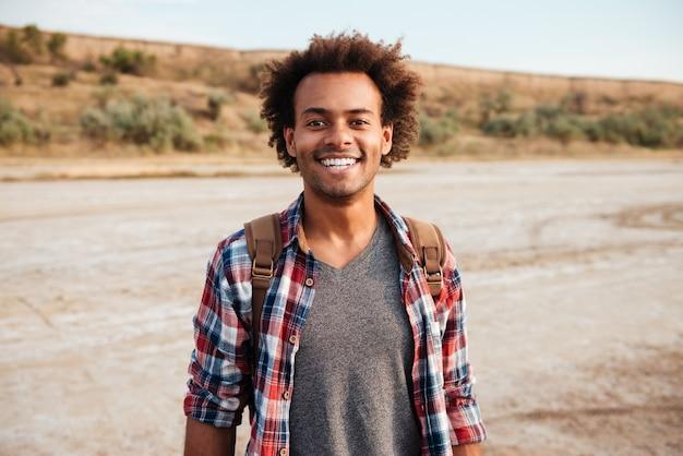 배낭과 격자 무늬 셔츠에 쾌활 한 아프리카계 미국인 젊은 남자의 초상화