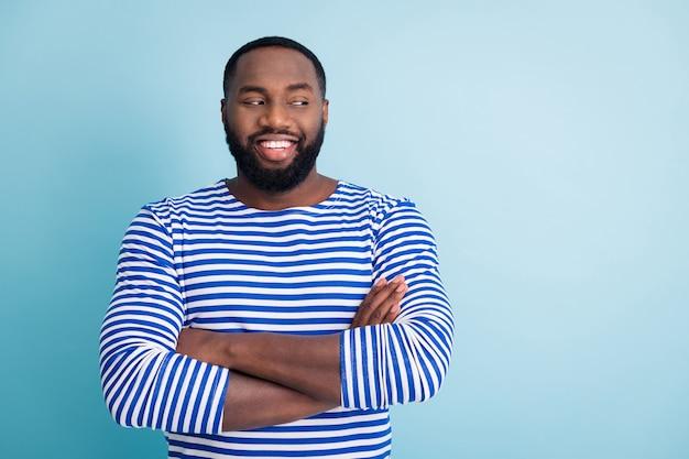 陽気なアフロアメリカンガイの仕事の肖像セーラーワーカークロスハンドルックコピースペース彼の友人の同僚が青い色の壁に隔離されたトレンディな航海ベストフロックを着ているのを聞く