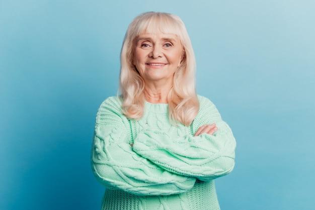 Портрет веселой пожилой женщины в возрасте стоит со скрещенными руками на синем фоне