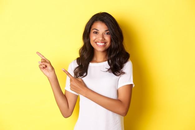 Портрет веселой и милой афро-американской девушки, указывая пальцами влево и улыбаясь, показывает