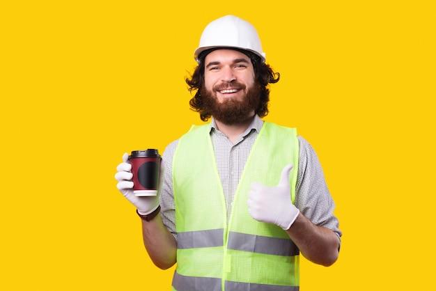 ヘルメットをかぶってコーヒーを片手に持ち帰り、親指を立てる陽気な建築家の肖像画