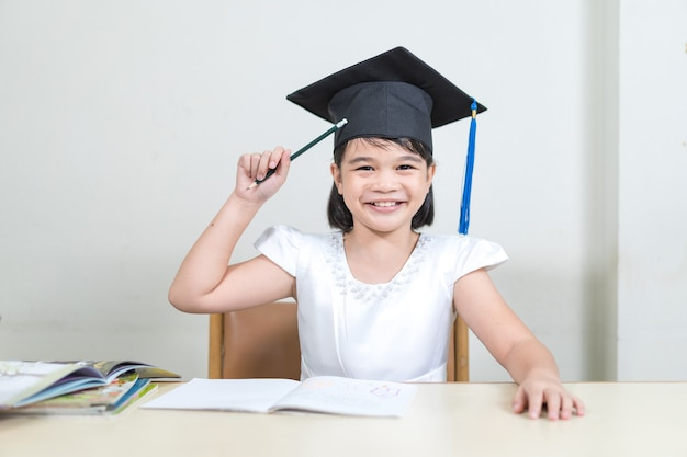 쾌활한 아시아 여학생의 초상화는 모타보드나 졸업 모자를 쓰고 연필을 잡고 흰색 배경에 복사 공간이 있는 공책에 글을 씁니다. 교육 졸업 개념 스톡 포토