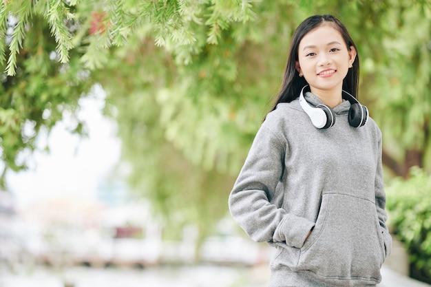 笑顔で、屋外でtsandingするときのパーカーの陽気なアジアの10代の少女の肖像画